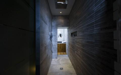 Une salle de bain aux murs en pierre, avec une douche au plafond, donne sur un spa